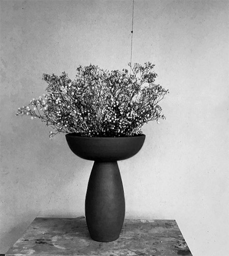 Black pedestal vase with dry flowers -- Nicolette Johnson